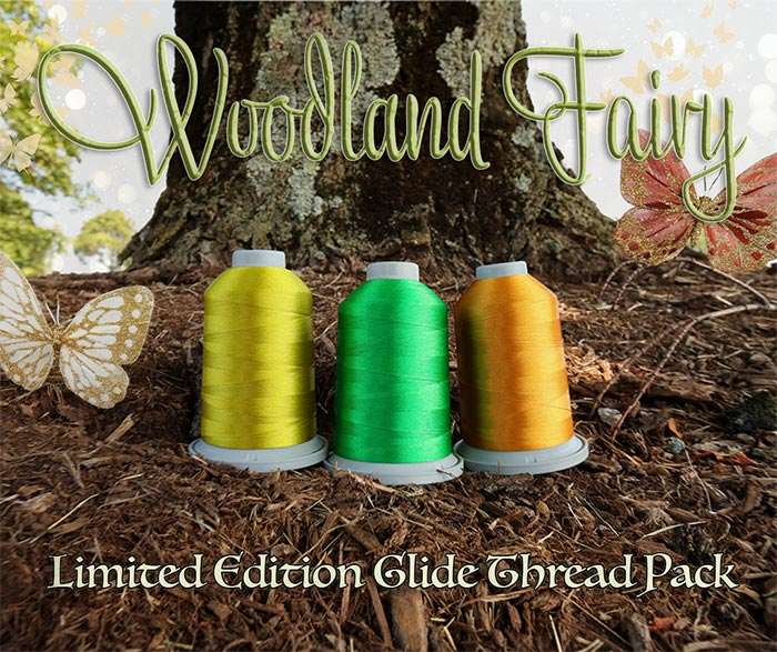 image of three cones of Glide thread with two glittery butterflies in front of a tree