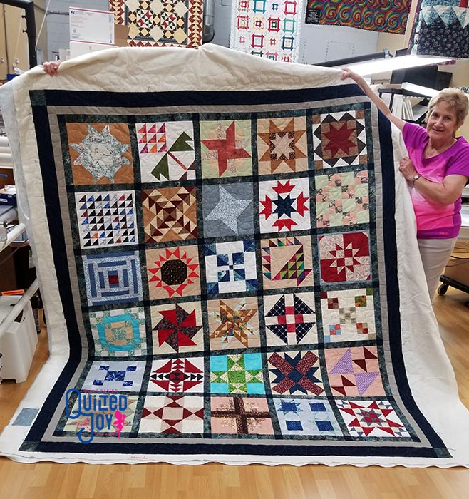 image of a woman holding up a sampler quilt