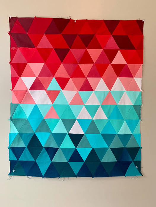 image of quilt made up of triangles in red, white, teal, and blue