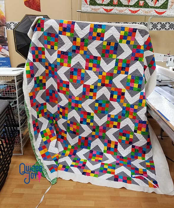 image of a quilt with lots of rainbow scrappy fabrics