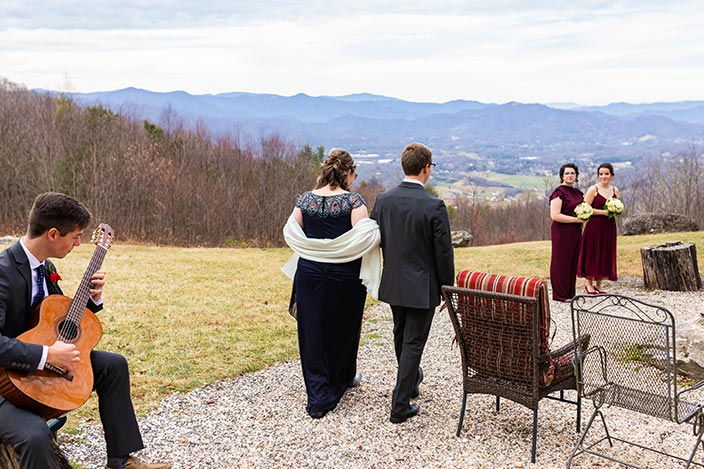 image of wedding on a mountaintop with musician playing guitar, bride walking down the path to meet bridesmaids at the altar