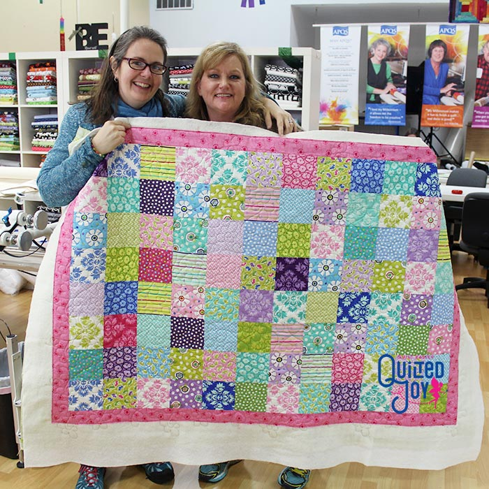 image of two women holding up a colorful quilt