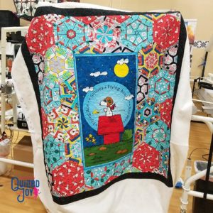 image of a quilt with a center illustration of Snoopy for the Peanuts comics on his red dog house surrounded by lots of color