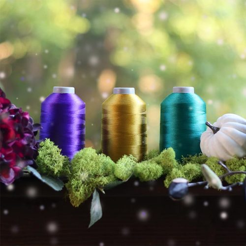 image of Glide thread cones in the Dark Fairy Glide Thread Pack surrounded by moss, flowers and leaves.